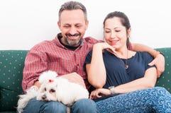 Retrato dos pares felizes que guardam o cachorrinho em casa fotos de stock