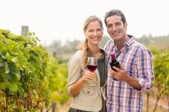 Retrato dos pares felizes que guardam o vidro e uma garrafa do vinho Imagens de Stock
