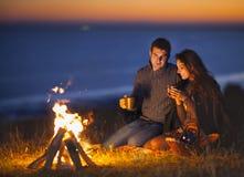 Retrato dos pares felizes que sentam-se pelo fogo na praia do outono Imagens de Stock Royalty Free