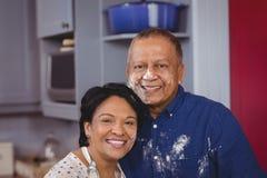 Retrato dos pares maduros que estão na cozinha imagens de stock