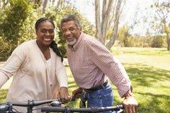 Retrato dos pares maduros que vão para o passeio do ciclo no parque Fotos de Stock Royalty Free