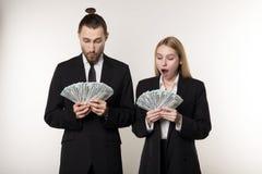 Retrato dos pares nos ternos pretos chocados guardando cédulas do dinheiro nas mãos imagem de stock