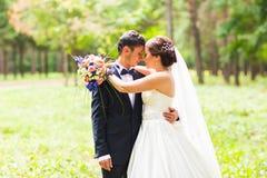 Retrato dos pares novos casados felizes exteriores Fotos de Stock Royalty Free