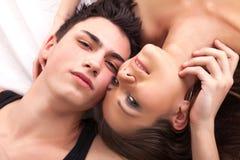 Retrato dos pares novos felizes que encontram-se na cama e no sorriso Fotografia de Stock