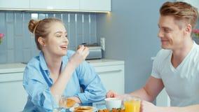 Retrato dos pares novos felizes que falam e que riem durante o café da manhã em casa filme