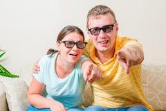 Retrato dos pares novos que olham a tevê nos vidros 3D Fotos de Stock
