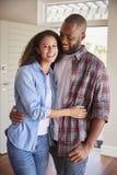 Retrato dos pares pela casa nova aberta de Front Door In Lounge Of imagem de stock royalty free