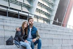 retrato dos pares pensativos que olham ausentes ao sentar-se em escadas Fotografia de Stock Royalty Free