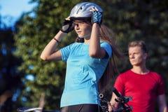Retrato dos pares profissionais do ciclismo que estão junto Outdoo Fotos de Stock