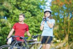 Retrato dos pares profissionais do ciclismo que estão junto Outdoo Imagens de Stock Royalty Free