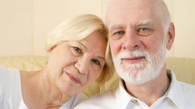 Retrato dos pares superiores bonitos alegres que sentam-se no sofá em casa Tendo o bom tempo que relaxa filme