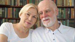 Retrato dos pares superiores bonitos alegres que sentam-se no sofá em casa Tendo o bom tempo que relaxa video estoque