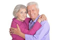 Retrato dos pares superiores felizes que levantam no fundo branco fotografia de stock