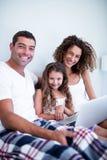 Retrato dos pares usando o portátil com sua filha na cama fotografia de stock royalty free
