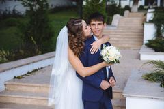 Retrato dos recém-casados que andam no parque A noiva no vestido de casamento está beijando seu marido no mordente, fotografia de stock royalty free