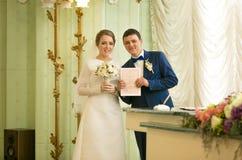 Retrato dos recém-casados que levantam no escritório de registro com engodo do casamento Imagens de Stock