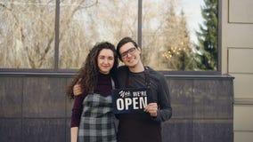 Retrato dos sócios comerciais felizes do casal que abrem o café e que guardam o ` nós somos placa aberta do ` na frente da janela video estoque