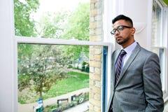Retrato dos vidros vestindo do homem de negócios indiano que estão pela janela Fotos de Stock Royalty Free