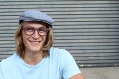 Retrato dos vidros vestindo louros ocasionais do homem novo, do chapéu do paperboy da notícia e do t-shirt azul do pescoço de gru Fotografia de Stock