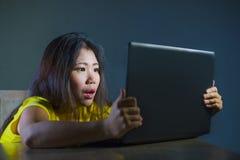 Retrato dramático de la muchacha del adolescente o de la mujer joven coreana asiática asustada y subrayada con el ordenador portá Fotos de archivo