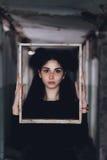 Retrato dramático de una muchacha hermosa joven Una muchacha con un aspecto agradable y una mirada triste Retrato creativo de una Foto de archivo libre de regalías