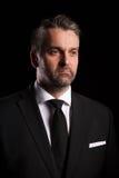 Retrato dramático del hombre de negocios en fondo negro foto de archivo