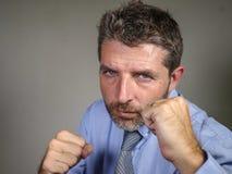 Retrato dramático del trastorno envejecido medio y del hombre de negocios feroz que presentan en la postura del boxeo que mira st foto de archivo