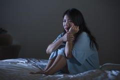 Retrato dramático do grito japonês asiático bonito e triste novo da mulher desesperado na cama acordada na depressão do sofriment imagens de stock royalty free