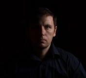 Retrato dramático de un hombre en un oscuro Imagenes de archivo