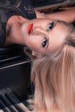 Retrato elegante da mulher loura no piano que olha a câmera Fotos de Stock