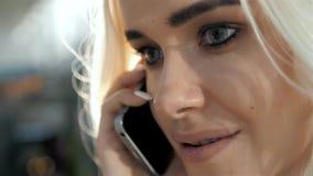 Retrato elegante de hablar rubio joven hermoso en el teléfono en el fondo de la calle que sonríe y que presenta en almacen de metraje de vídeo