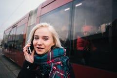 Retrato elegante de la calle de una mujer joven y hermosa que habla por el teléfono en un fondo del tren rojo Imágenes de archivo libres de regalías