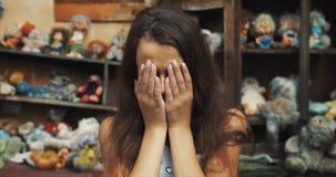 Retrato emocional da menina triste da criança pequena que olha desesperadamente a câmera metragem 4k vídeos de arquivo