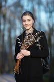 Retrato emocional de la mujer hermosa feliz joven con un ramo de gatito-sauces que llevan la capa negra que da un paseo en la igu Imágenes de archivo libres de regalías