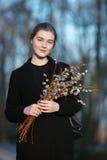 Retrato emocional de la mujer hermosa feliz joven con un ramo de gatito-sauces que llevan la capa negra que da un paseo en la igu Imagen de archivo libre de regalías