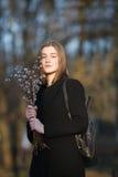 Retrato emocional de la mujer hermosa feliz joven con un ramo de gatito-sauces que llevan la capa negra que presenta en parque de Imagenes de archivo