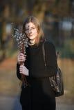 Retrato emocional de la mujer hermosa feliz joven con un ramo de gatito-sauces que llevan la capa negra que presenta en parque de Foto de archivo libre de regalías