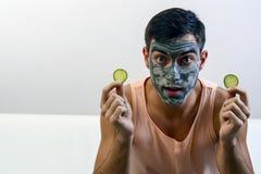 Retrato emocional de un hombre en una máscara de la arcilla en su cara con los pepinos en sus manos Cuidado de piel Copie el espa foto de archivo libre de regalías