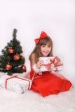 Retrato emocional de una muchacha alegre en vestido rojo El regalo del Año Nuevo debajo del árbol Foto de archivo