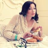 Retrato emotivo de uma mulher bonita nova que come seu croissant fotografia de stock royalty free