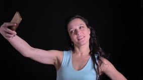 Retrato en el perfil de la mujer de mediana edad que hace las selfie-fotos en smartphone con la satisfacción en fondo negro almacen de metraje de vídeo