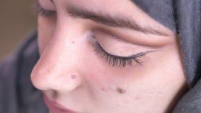 Retrato en el perfil de las manos femeninas que dibujan flechas negras usando el cepillo fino para la mujer musulmán atractiva en almacen de video