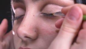 Retrato en el perfil de las manos femeninas que dibujan flechas negras usando el cepillo fino para la mujer musulmán hermosa en h almacen de metraje de vídeo
