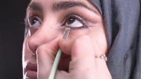 Retrato en el perfil de las manos femeninas que dibujan flechas negras usando el cepillo plano para la mujer musulmán hermosa en  metrajes