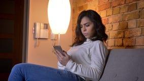 Retrato en perfil de la empresaria morena caucásica con vueltas del smartphone a la cámara y sonrisas en la atmósfera casera almacen de metraje de vídeo