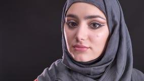 Retrato en perfil de la mujer musulmán hermosa en hijab con vueltas de moda del maquillaje a la cámara y a los relojes tranquilam metrajes
