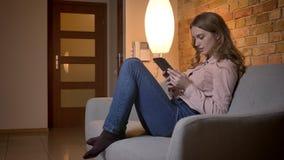 Retrato en perfil del adolescente rubio joven que se sienta en el sofá y que mira atento en la tableta en hogar acogedor metrajes