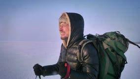 Retrato en perfil del backpacker agotado con los palillos de la montaña y los paseos enormes del bolso con dificultad a lo largo  almacen de metraje de vídeo