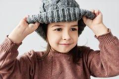 Retrato encantador de la niña caucásica que juega con el suéter gris caliente del sombrero del invierno, de la sonrisa y el lleva imágenes de archivo libres de regalías