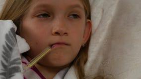 Retrato enfermo del niño con el termómetro, muchacha enferma en cama, niño triste que sufre 4K frío almacen de metraje de vídeo
